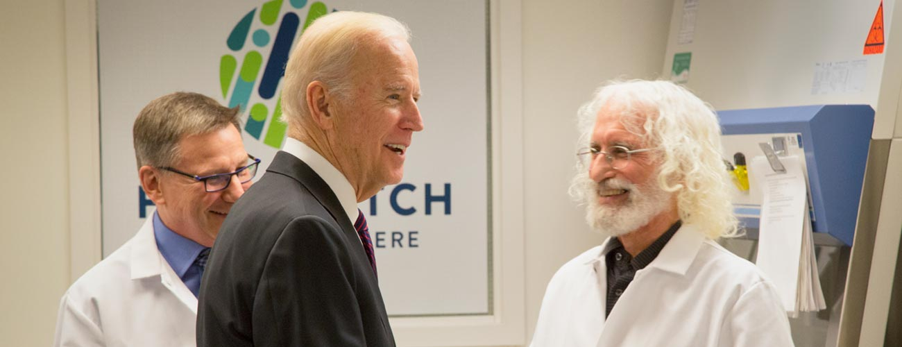 Vice President Joe Biden talks to cancer immunotherapy researchers Dr. Stan Riddell, left, and Dr. Phil Greenberg during a Fred Hutch lab tour.